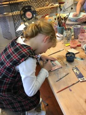 Practicing scratching a design in the glaze.